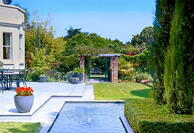The main room of this family country garden has a large water feature.